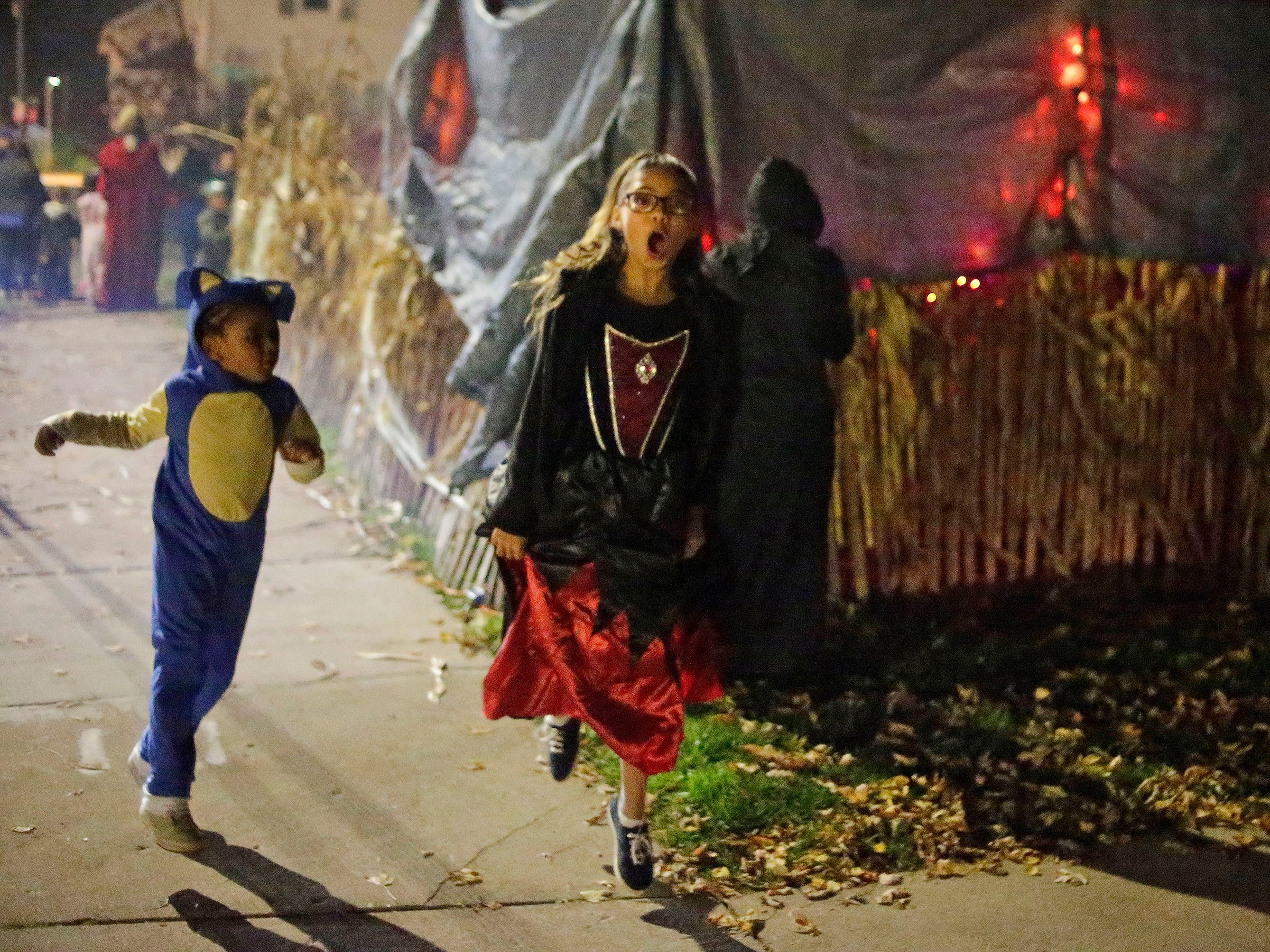 Trick or Treaters leave screaming from Scott Grunert's haunted yard during Trick or Treat, Wednesday, October 31, 2018, in Sheboygan, Wis.