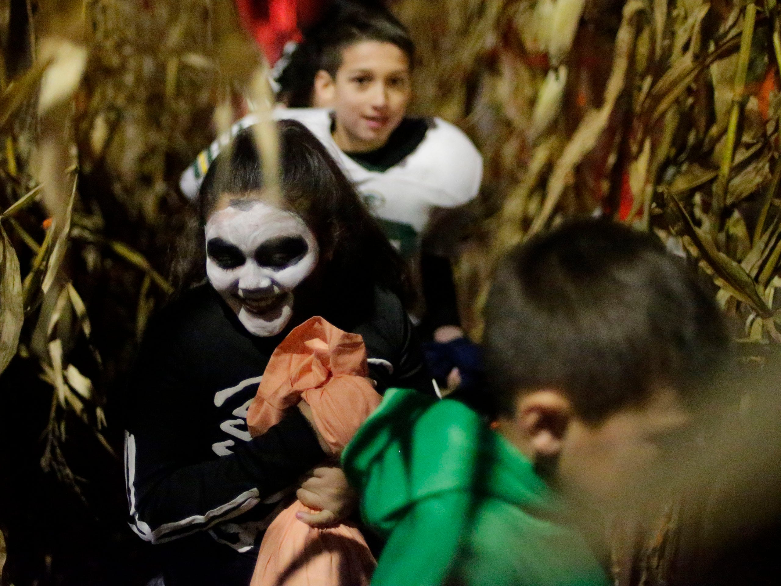 Trick or Treaters scamper through Scott Grunert's corn maze at his haunted yard, Wednesday, October 31, 2018, in Sheboygan, Wis.