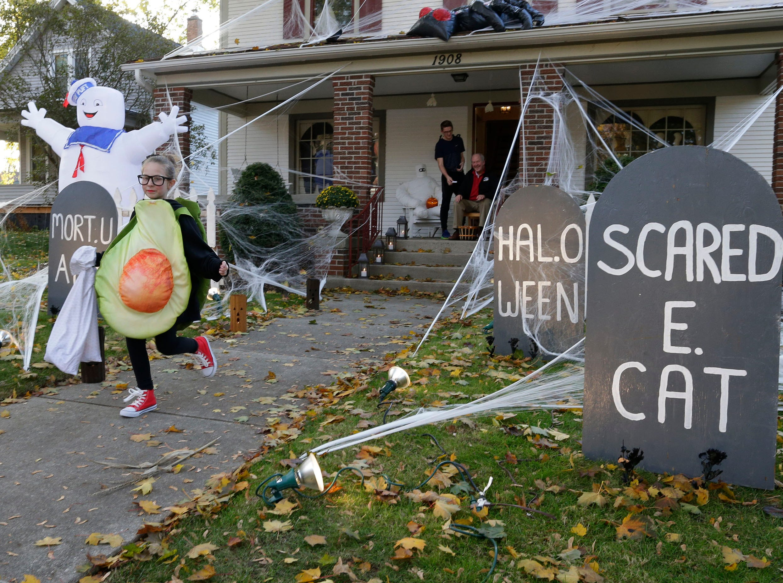 A trick or treater scampers from a house on North Sixth Street during Trick or Treat, Wednesday, October 31, 2018, in Sheboygan, Wis.