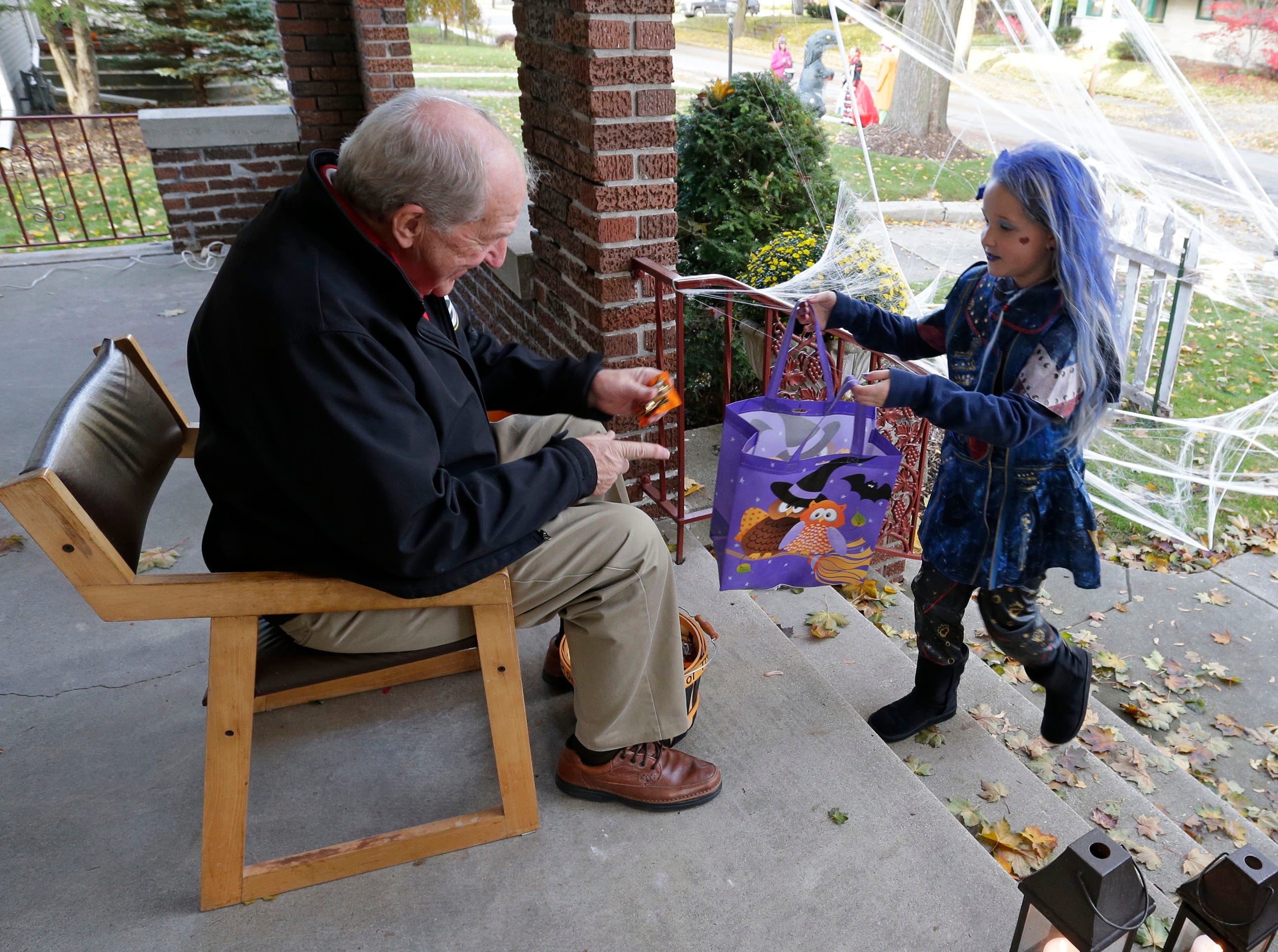 Ken Leibham hands out candy during Trick or Treat, Wednesday, October 31, 2018, in Sheboygan, Wis.
