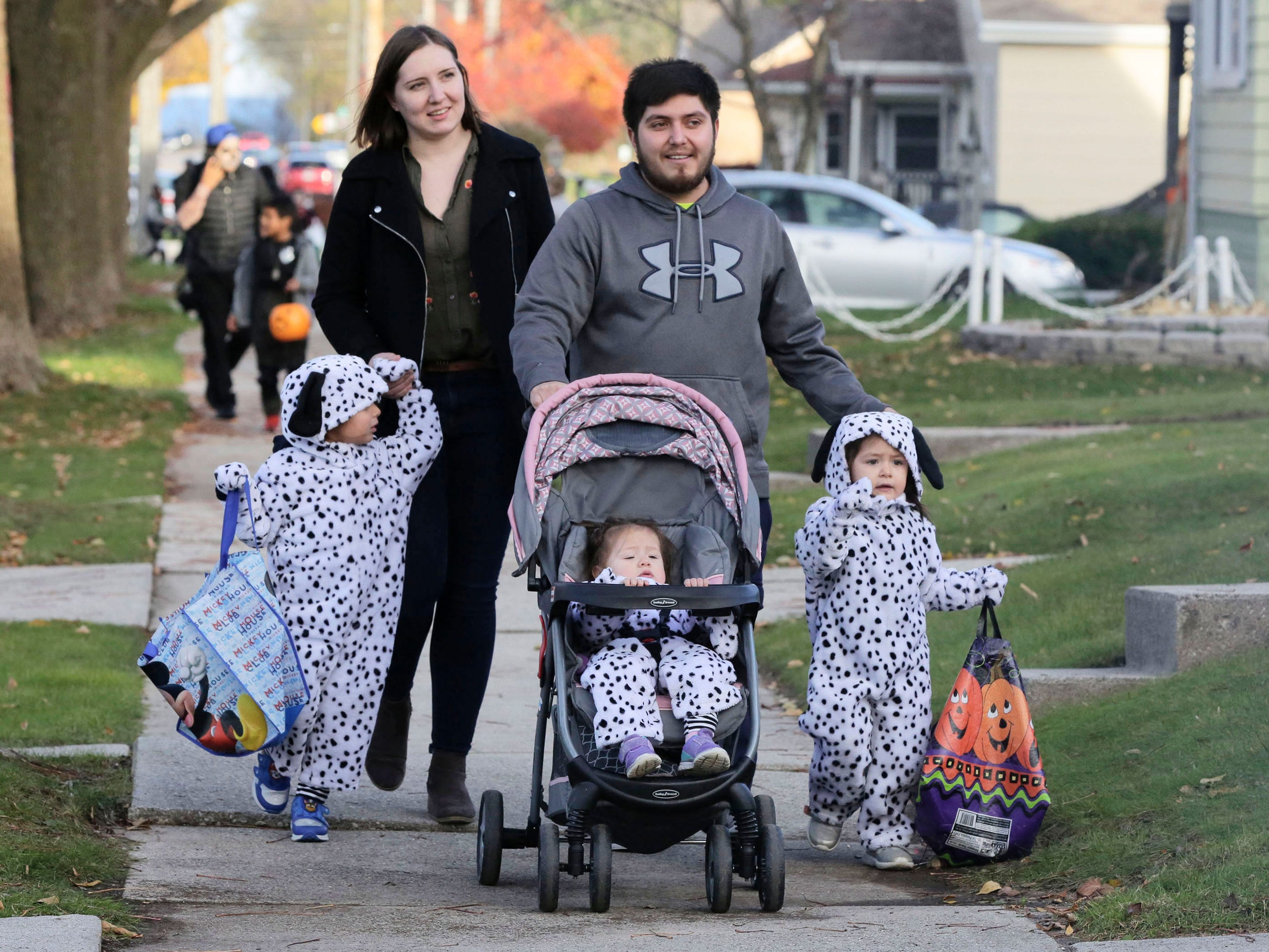 Eleanor Bonilla, 4, walks with her mom Katie Gibbs, her dad Martin Bonilla, her baby sister Anabelle, 1, and her other sister Daisy, 2, during Trick or Treat, Wednesday, October 31, 2018, in Sheboygan, Wis.