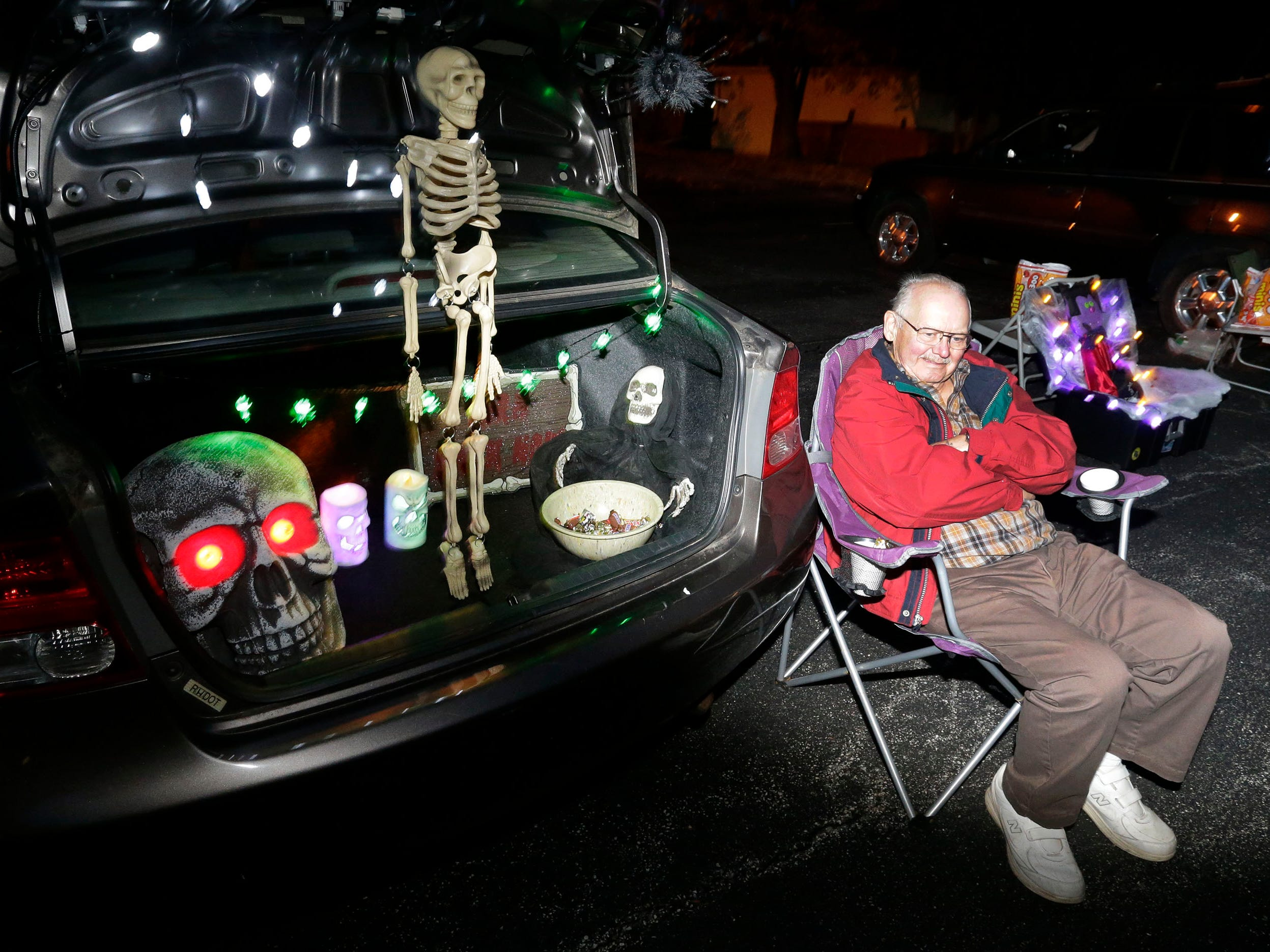 Tom Beauchaine of Ishpeming, Michigan sits by a Trunk or Treat at St. Peter Lutheran Church during Trick or Treat, Wednesday, October 31, 2018, in Sheboygan, Wis.