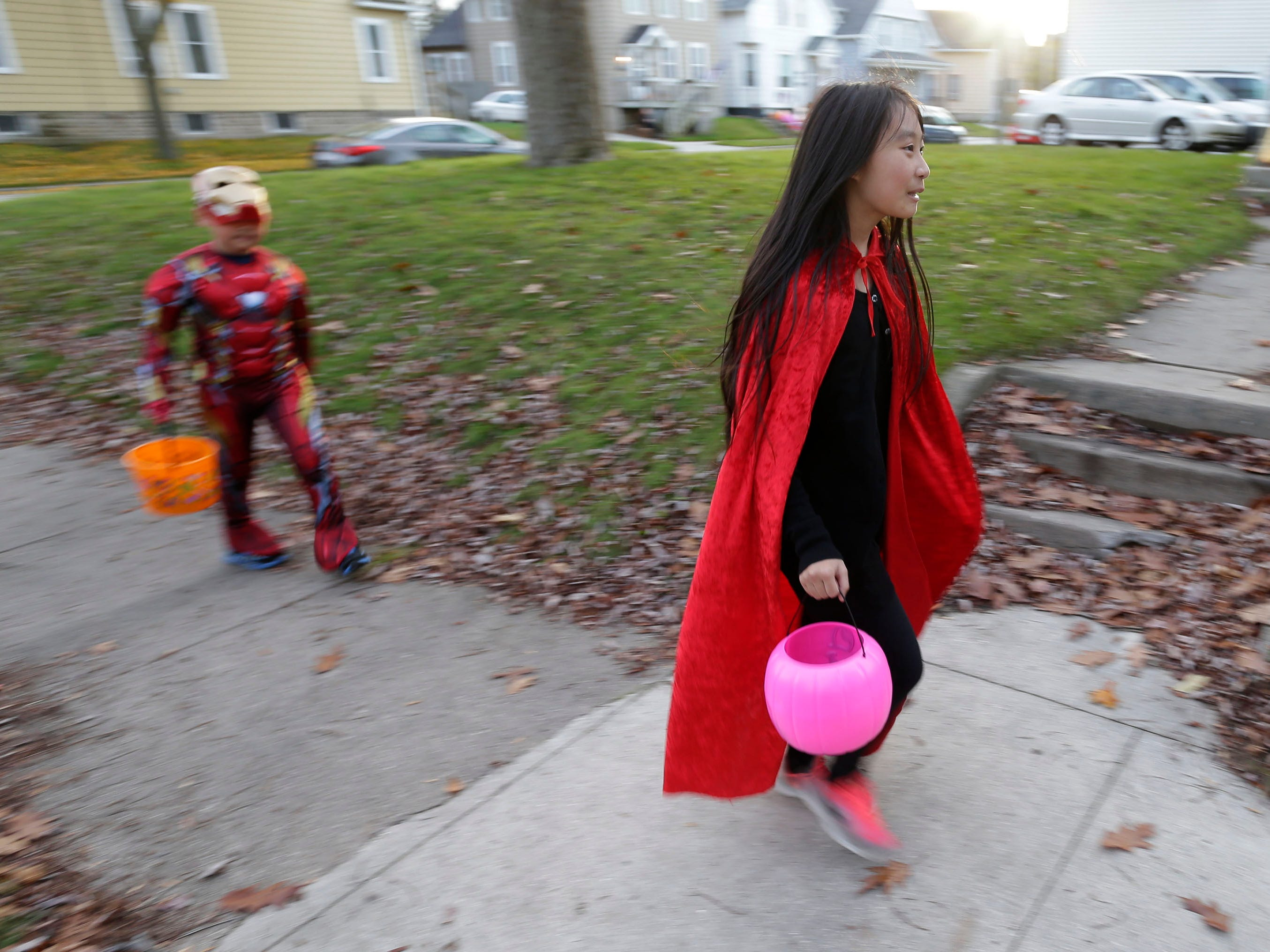Alexander Lee, 7, left, folllows his sister Jasmine, 7, during Trick or Treat, Wednesday, October 31, 2018, in Sheboygan, Wis.