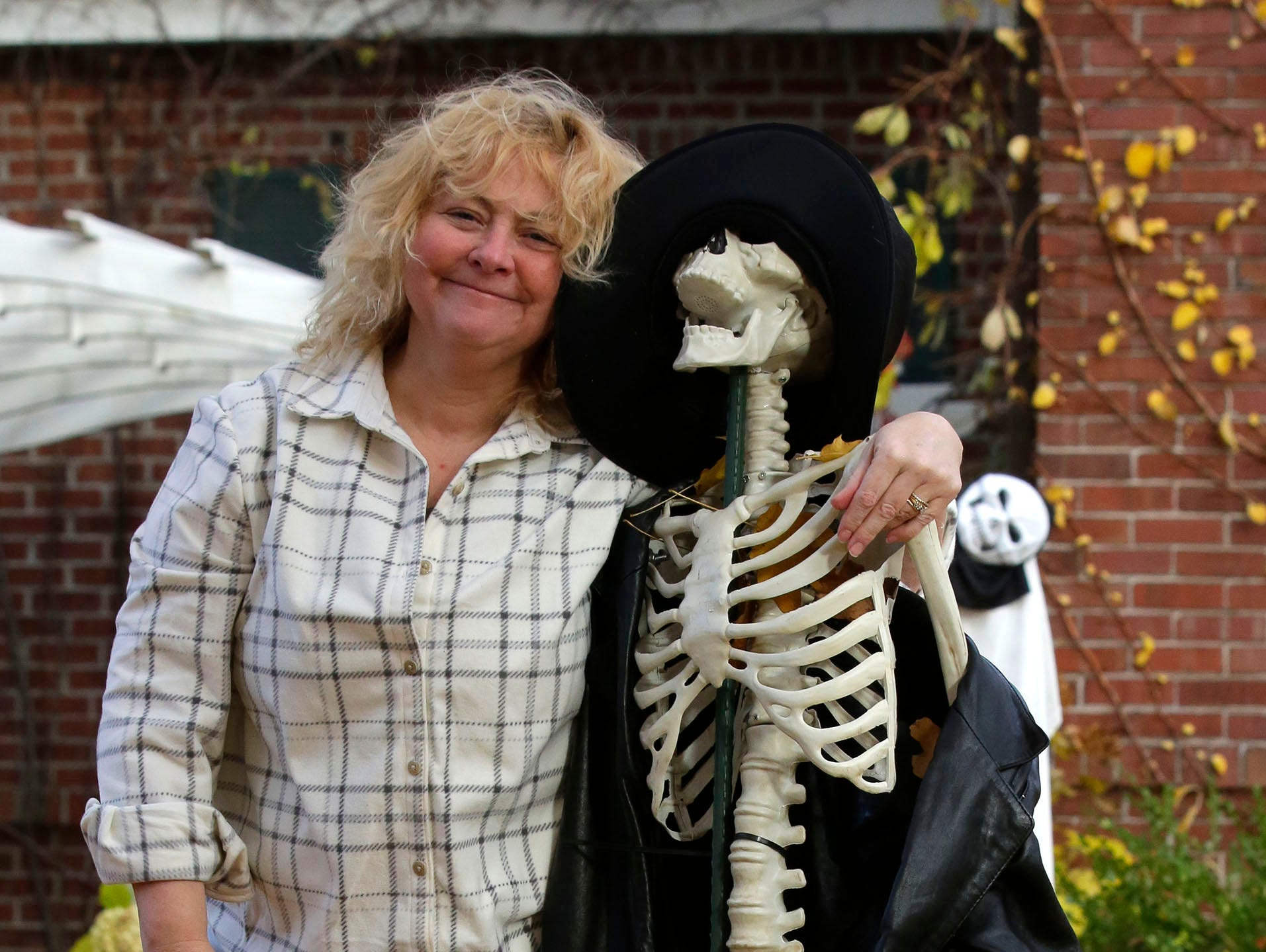 Sarah Fritz of Sheboygan poses with one of her scary skeletons during Trick or Treat, Wednesday, October 31, 2018, in Sheboygan, Wis.