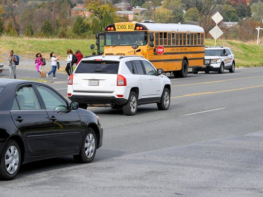 Deputy Steve Davis of the Augusta County SheriffÕs Office shadows a school bus as it makes a stop in Verona on Thursday, Nov. 1, 2018. He keeps an eye open for drivers that might try to pass the bus while it is stopped. Since January 1, Davis has handed out over 100 tickets related to drivers failing to stop for a stopped school bus.