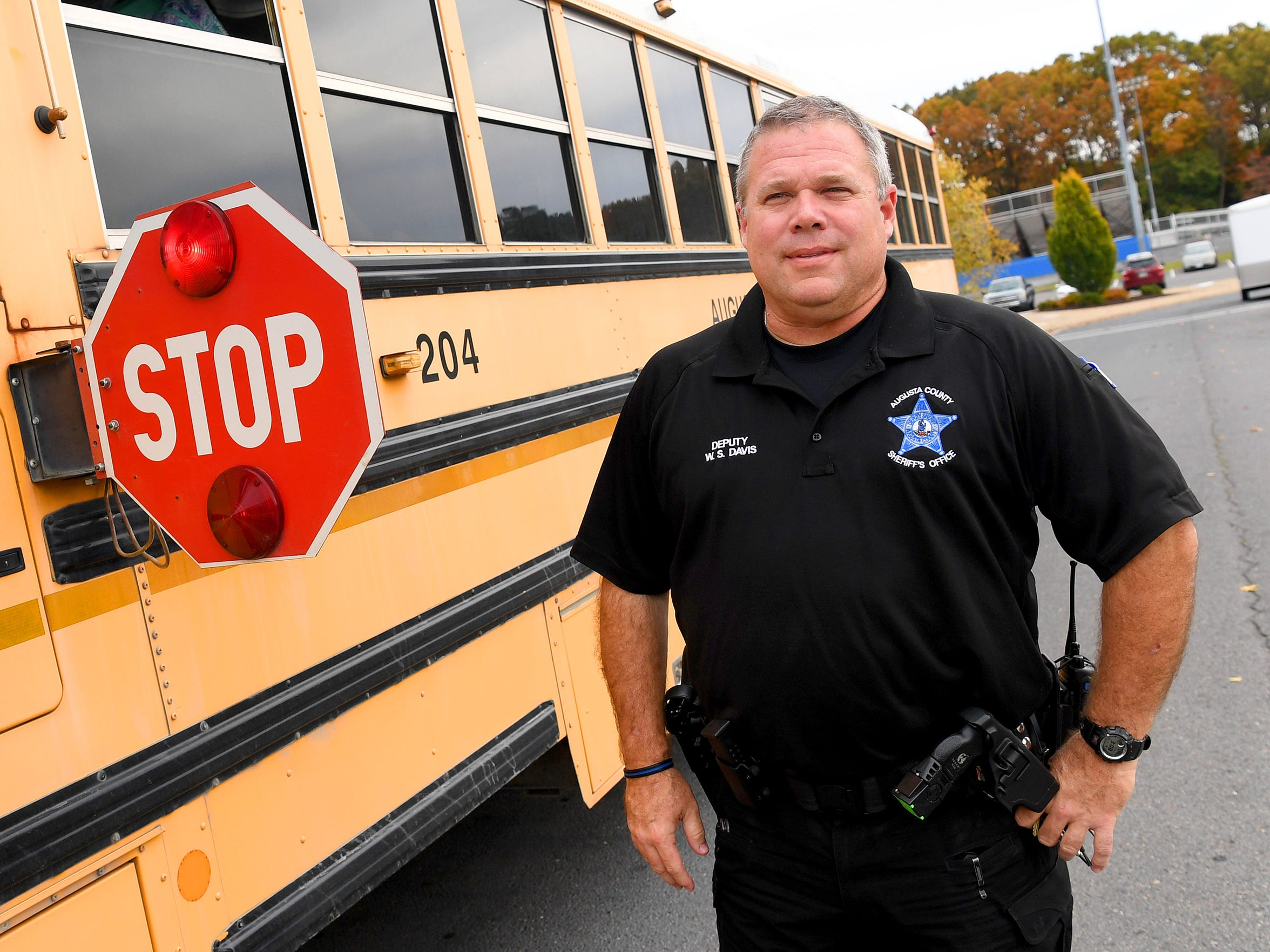 Deputy Steve Davis of the Augusta County Sheriff's Office has handed out over 100 tickets related to drivers failing to stop for a stopped school bus. He is photographed alongside a school bus at Fort Defiance High School on Thursday afternoon, Nov. 1, 2018.