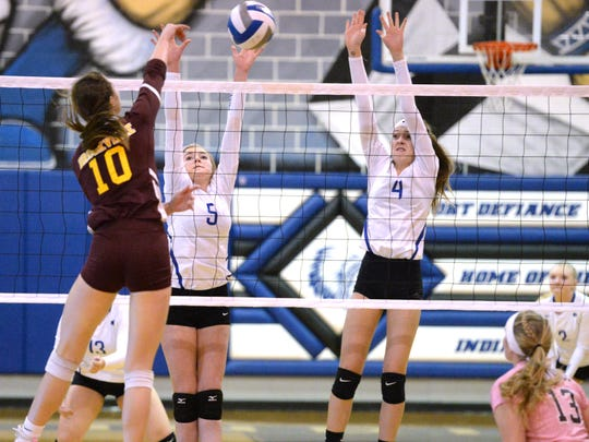 Lani Goggin (4) and Maddie Painter (5) go up to block Brookville's Parker Morrison Wednesday in the regional quarterfinals.