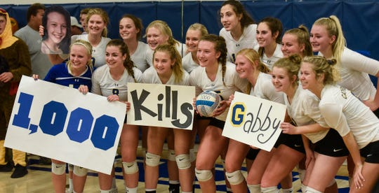 Team members gather to celebrate Gabby Heying's 1,000th kill following  the Tuesday, Oct. 30, Section 6-2A volleyball quarterfinals game against Melrose at Cathedral High School in St. Cloud.