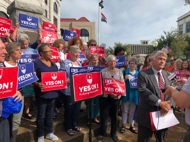 "FILE - In this Aug. 31, 2018 file photo, supporters of Missouri's redistricting ballot measure hold signs behind former state Sen. Bob Johnson as he serves as their spokesman during a press conference outside the Cole County Courthouse in Jefferson City, Mo. Proposed state Constitutional Amendment 1 on the Nov. 6, 2018, ballot would require Missouri state House and Senate districts to be drawn to achieve ""partisan fairness"" and ""competitiveness."" (AP Photo/David A. Lieb, File)"