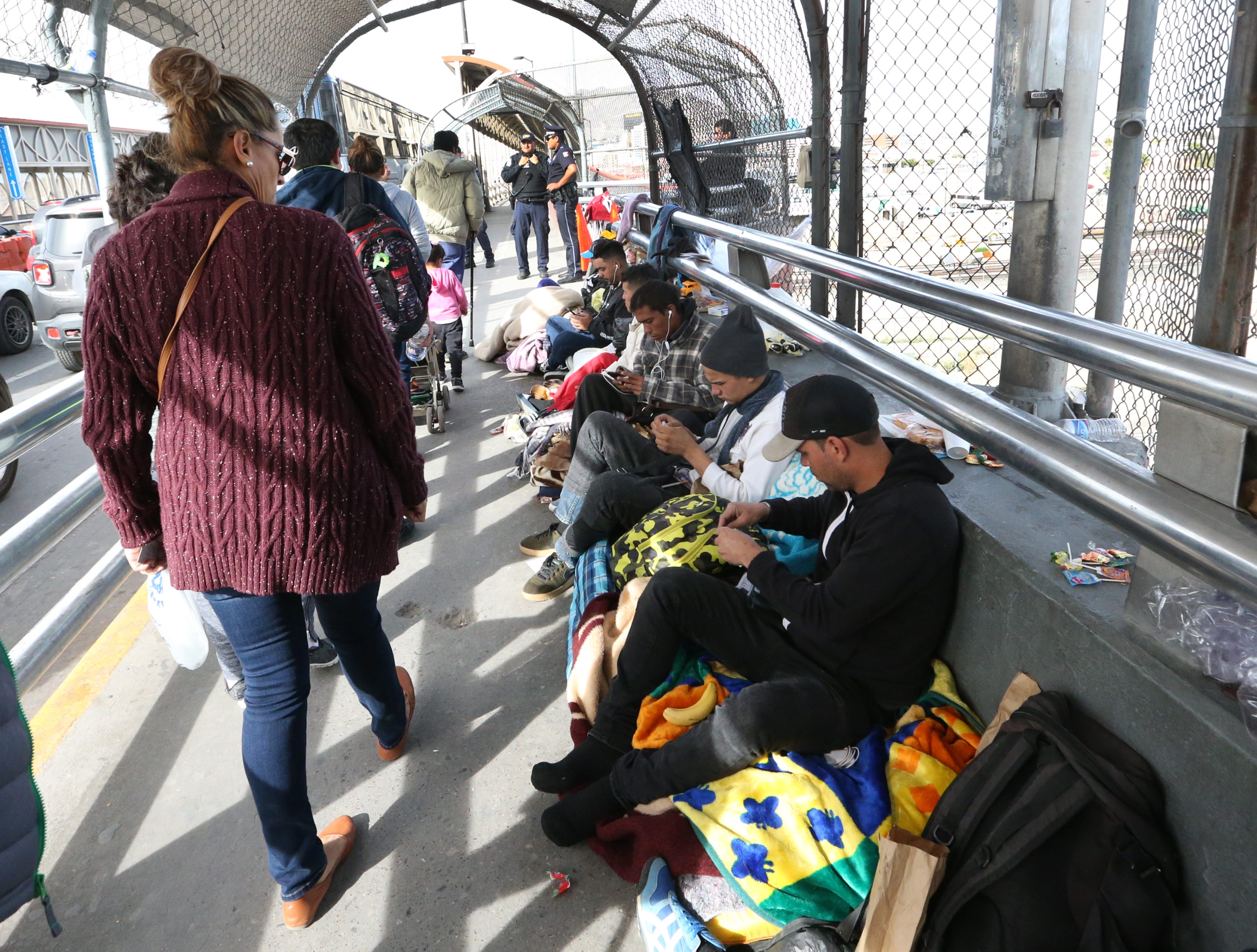 Documented border crossers walk past a group of undocumented migrants waiting to enter the U.S. atop the Paso Del Norte international Bridge Thursday. Just over 100 migrants were camped out at the bridge.