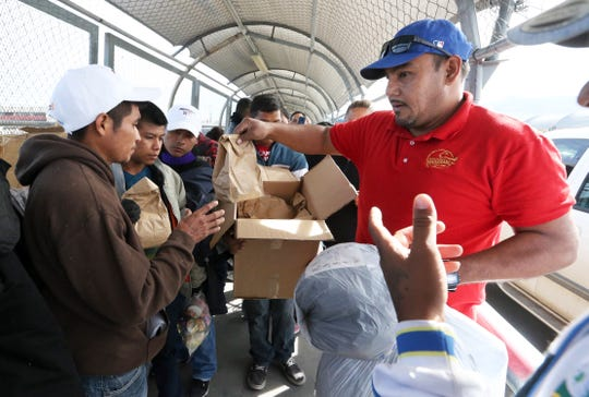 Hugo Enrique Lujan, right, of Mahanaim Christian church in Juárez, hands out sack lunches to migrants waiting to enter the U.S. atop the Paso Del Norte international bridge Thursday afternoon. Just over 100 immigrants from places including Mexico, Central America and Cuba were camped out at the bridge. U.S. immigration officials were allowing small groups at a time to enter.