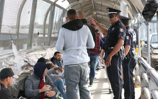 Mexican federal police try to keep the pedestrian walkway of the Paso Del Norte international bridge clear for documented border crossers as a group of about 100 undocumented migrants sit and wait to enter the U.S. Thursday.
