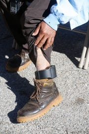 A recently released immigrant wears an ankle bracelet used to track migrants who have been released from federal custody. The migrant was at an El Paso motel awaiting transportation to be united with relatives.
