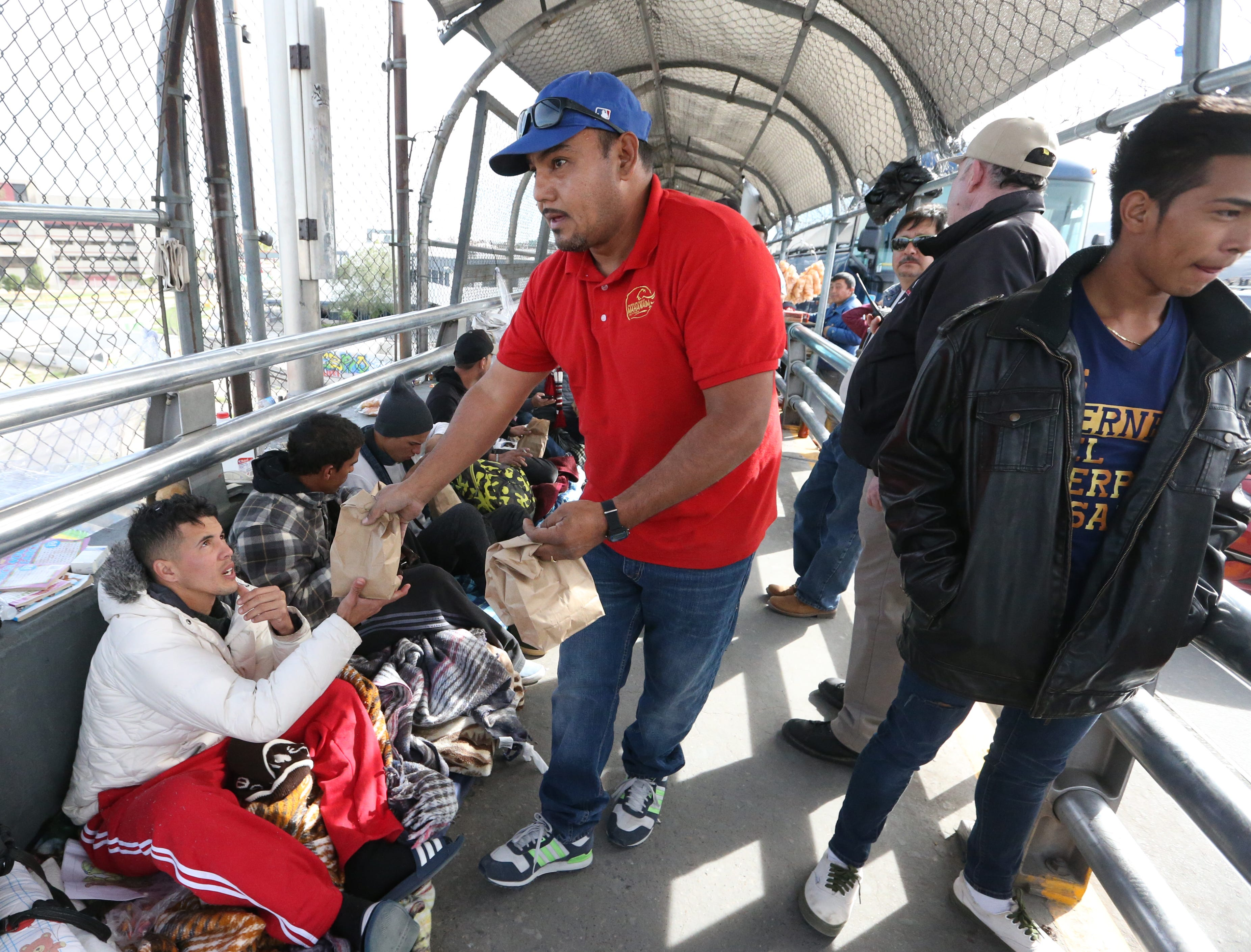 Hugo Enrique Lujan, center, of Mahanaim Christian church in Juarez hands out sack lunches to migrants waiting to enter the U.S. atop the Paso Del Norte international bridge Thursday afternoon. Just over 100 immigrants from various countries, including Mexico, Central America and Cuba were camped out at the bridge. U.S. immigration officials were allowing small groups at a time to enter.