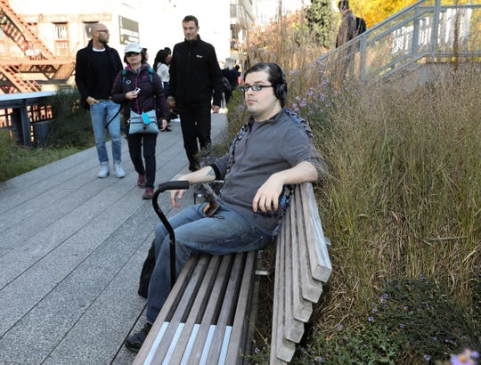 Steven Ciccone, 35, sits on a bench on the High Line in the Chelsea section of New York City on Wednesday, October 31, 2018.  Ciccone was born with cerebral palsy, he's suing Metro-North for the brain injury he says he sustained after Hudson Line Train 8808 crashed in the Bronx on Dec. 1, 2013, killing four and injuring dozens of others.