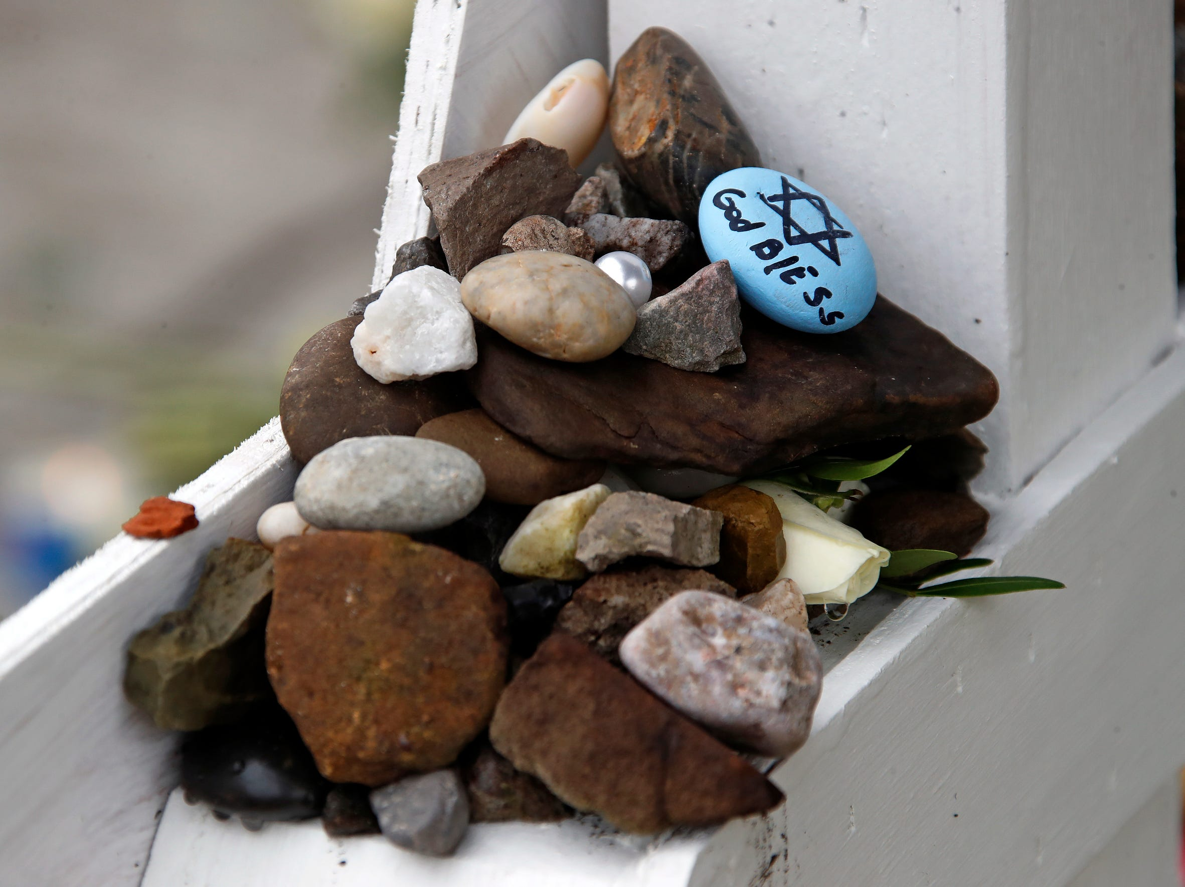Stones are placed Thursday, on the stars of David bearing the names of the shooting victims at Tree of Life Synagogue.