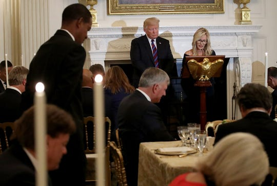 President Donald Trump bows his head as Pastor Paula White delivers a prayer before dinner for guests celebrating evangelical leadership at the White House in August.