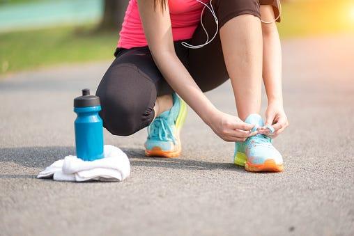 Female hands tying shoelace on running shoes, Runner getting ready in the early morning at park