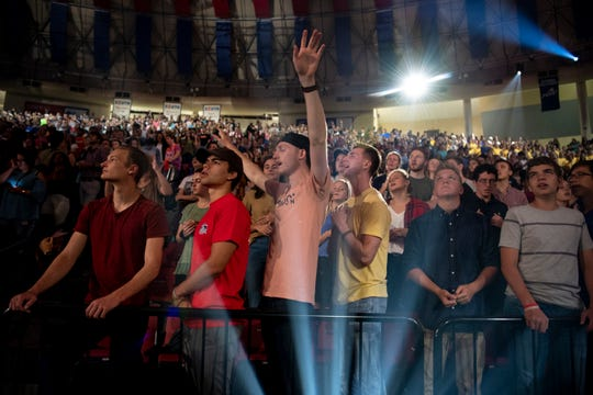 """Students cheer and sing as Liberty University's student band, """"Liberty Worship Collective,"""" opens a convocation ceremony in the Vines Center on Sept. 26."""