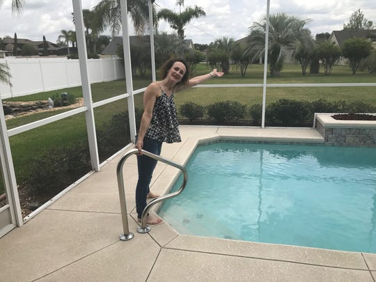 Jodi Meyers stands by the pool at the house she bought.