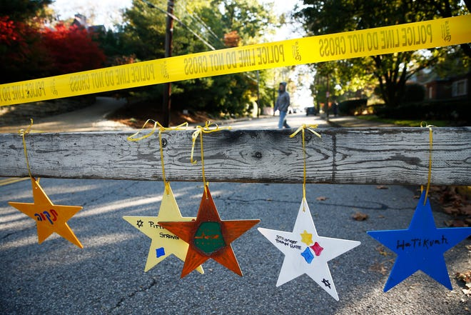 """Stars with messages like """"Pittsburgh Strong"""" and """"Stronger Than Hate"""" hang off of a police barrier near the Tree of Life synagogue in Pittsburgh, Pennsylvania."""