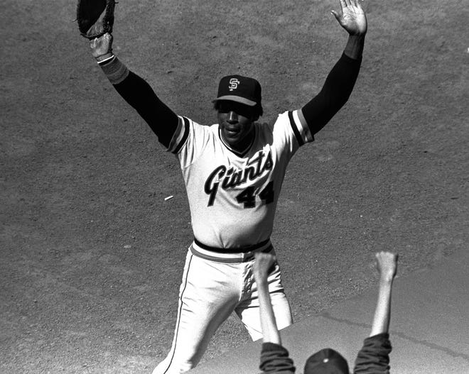 Willie McCovey of the San Francisco Giants raises his hands in salute to the cheering crowd after he was replaced in the lineup in a game with the Cincinnati Reds, July 3, 1980.  It was the last home game appearance before retirement for the popular veteran.