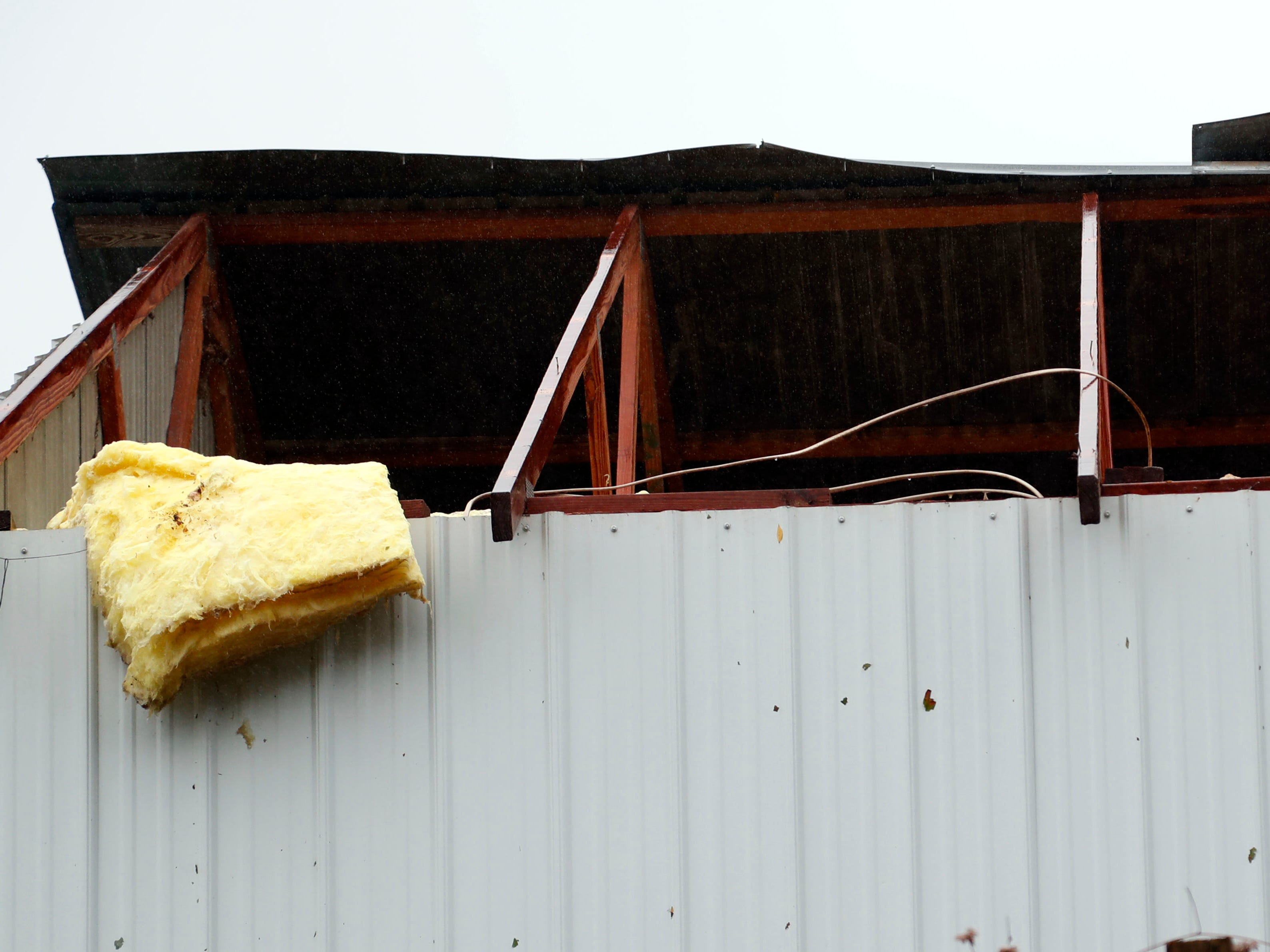A heavy winds from a storm damaged this farm shop roof in Roxie, Miss.