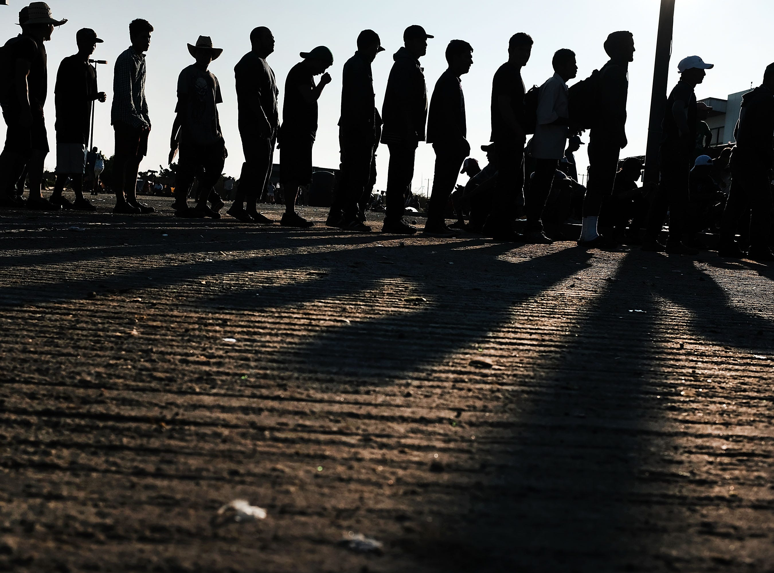 Members of the Central American caravan line up at dawn for food in a camp on Oct. 31, 2018 in Juchitan de Zaragoza, Mexico. The group of migrants, many of them fleeing violence in their home countries, took a rest day on Wednesday and plan to resume their march towards the United States border on Thursday. As fatigue from the heat, distance and poor sanitary conditions has set in, the numbers of people participating in the march has slowly dwindled, but a significant group are still determined to get to the United Sates. It has been widely reported that the Pentagon will deploy 5,200 active-duty troops to the U.S.-Mexico border in an effort to prevent members of the migrant caravan from illegally entering the country.