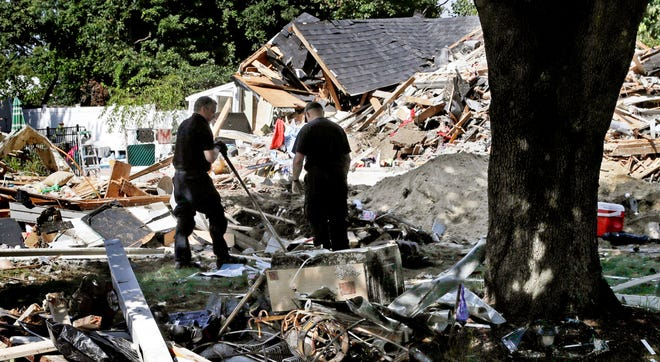 In this Sept. 21, 2018 file photo, fire investigators pause while searching the debris at a home which exploded following a gas line failure in Lawrence, Mass.  Federal prosecutors have been conducting a criminal investigation into the natural gas explosions and fires that rocked three communities north of Boston in September.