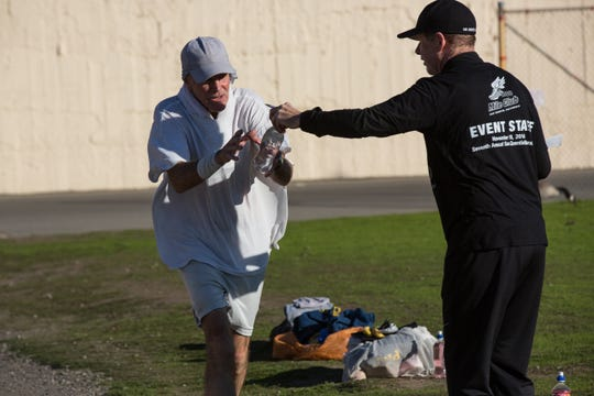 San Quentin State Prison 1,000-mile club coach Frank Ruona (right), hands a water bottle to marathoner Michael Keeyes, left, on the 26.2 mile course behind bars. The inmates at San Quentin have to run 105 laps around the lower recreation yard to complete the race.