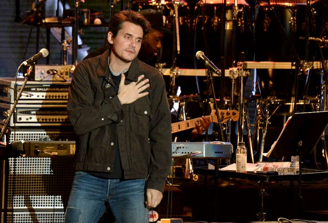 John Mayer puts his hand on his heart while paying tribute to Mac Miller during a show at the Greek Theatre on October 31.