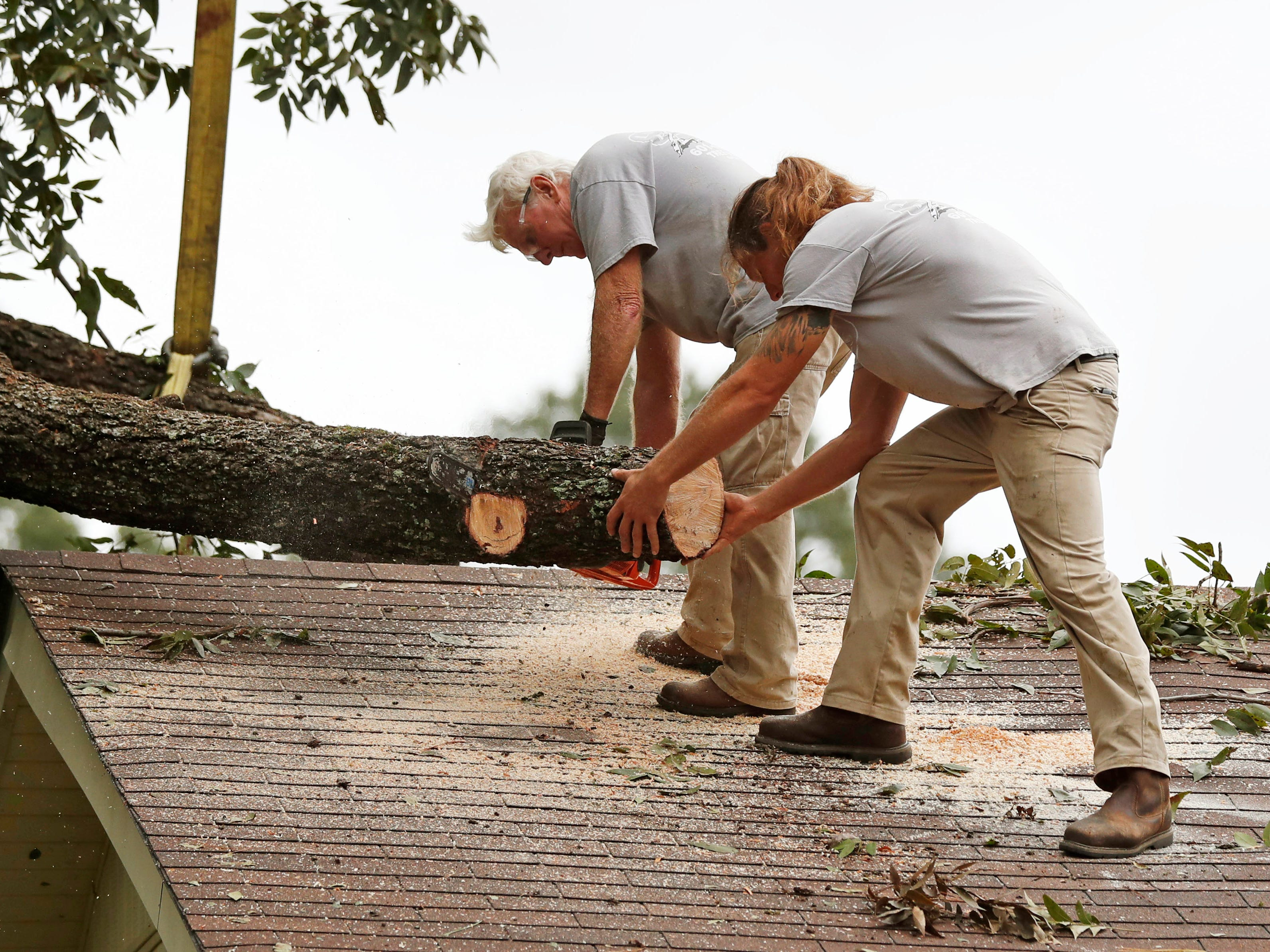 Chuck Smith, left and Phillip Johnson cut into a large section of a pecan tree branch that fell on the roof of this Natchez, Miss., home early on, Nov. 1, 2018. Strong storms and several possible tornadoes hit throughout Mississippi causing widespread damage.