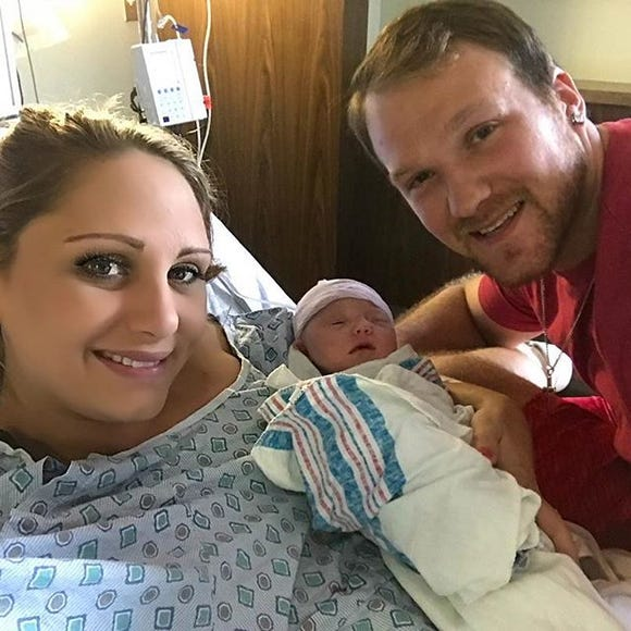 Breast cancer survivor Meghan Koziel with her newborn daughter and husband, John, on Sept. 15, 2018.