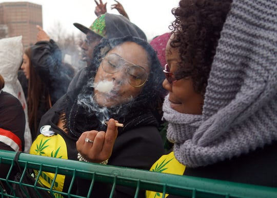 Kennya Anderson of Chicago passes a joint to her friend as marijuana smoke trickles from her lips during the Denver 420 rally.