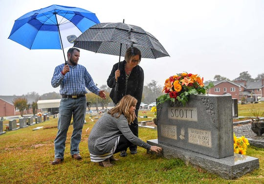 Jennifer Rigdon places pennies at the gravestone of her grandmother Barbara Scott, near her husband Shafford Rigdon and mother Pam Isbell, right, at Lebanon Baptist Church in Pendleton on Friday.  Husband and wife Michael and Cathy Scott, 59 and 60, and their mothers, 80-year-old Barbara Scott and 82-year-old Violet Taylor were killed in the Refuge Road home in Pendleton in November 2015, an unsolved case the family hopes will get solved.