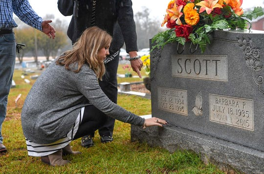 Jennifer Rigdon places pennies at the gravestone of her grandmother Barbara Scott at Lebanon Baptist Church in Pendleton on Friday.  Husband and wife Michael and Cathy Scott, 59 and 60, and their mothers, 80-year-old Barbara Scott and 82-year-old Violet Taylor were killed in the Refuge Road home in Pendleton in November 2015, an unsolved case the family hopes will get solved.