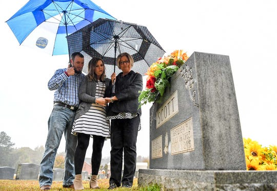 Jennifer Rigdon, middle, her husband Shafford Rigdon, left, and mother Pam Isbell, right, visit the gravestone of her grandmother Barbara Scott, near  at Lebanon Baptist Church in Pendleton on Friday.  Husband and wife Michael and Cathy Scott, 59 and 60, and their mothers, 80-year-old Barbara Scott and 82-year-old Violet Taylor were killed in the Refuge Road home in Pendleton in November 2015, an unsolved case the family hopes will get solved.