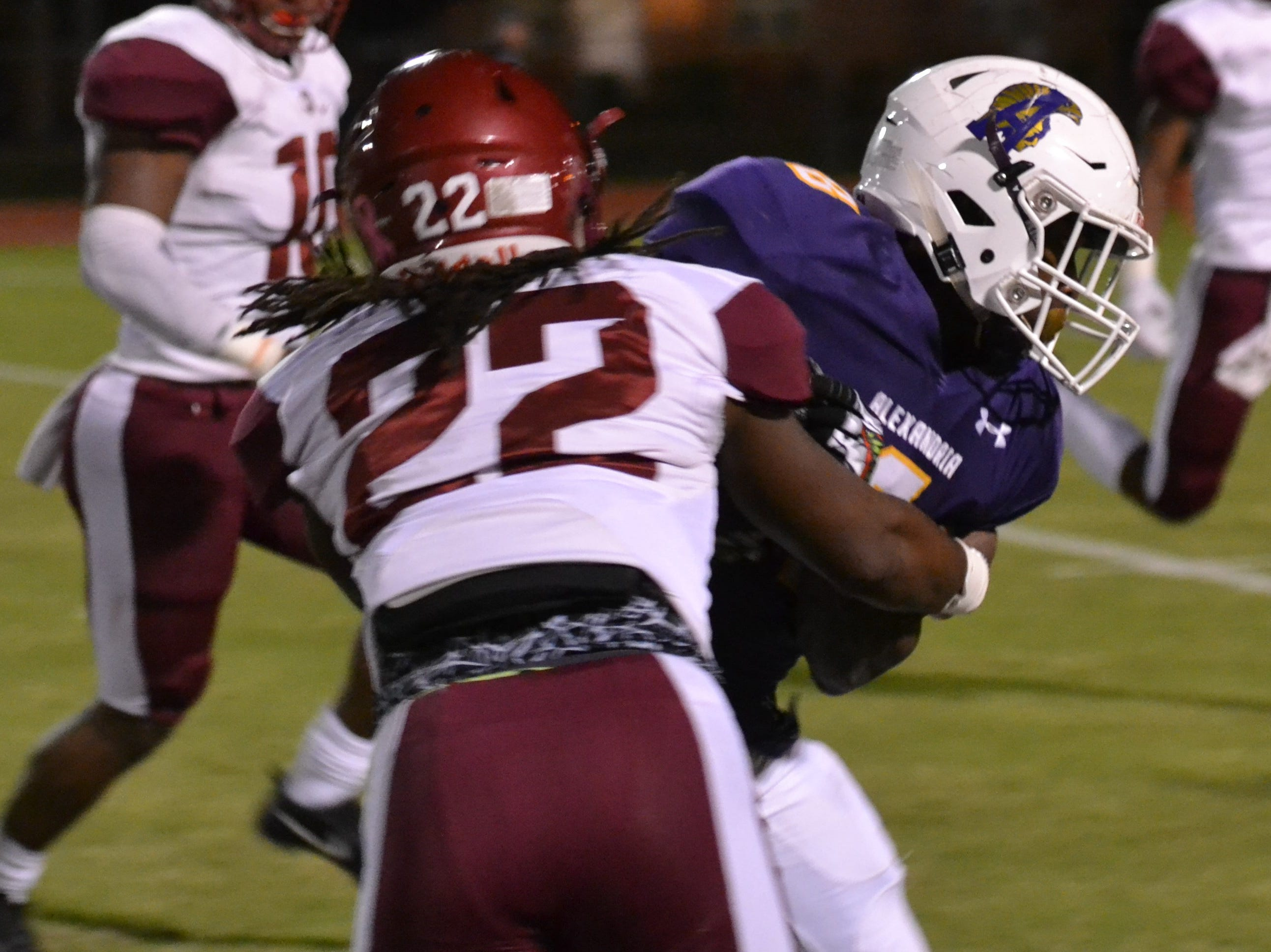 Richard Chark fights for yards as he tries to break the tackle of Ouachita's Elijah Hall (22). The ASH Trojans fell to the Ouachita Parish Lions 42-20 Thursday, Nov. 1, at Alexandria Senior High.