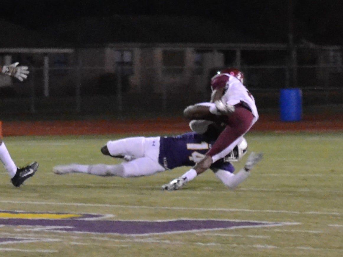ASH defender Latrell Holly (14) makes a touchdown-saving tackle on Ouachita's Chaunzavia Lewis (2). The ASH Trojans fell to the Ouachita Parish Lions 42-20 Thursday, Nov. 1, at Alexandria Senior High.