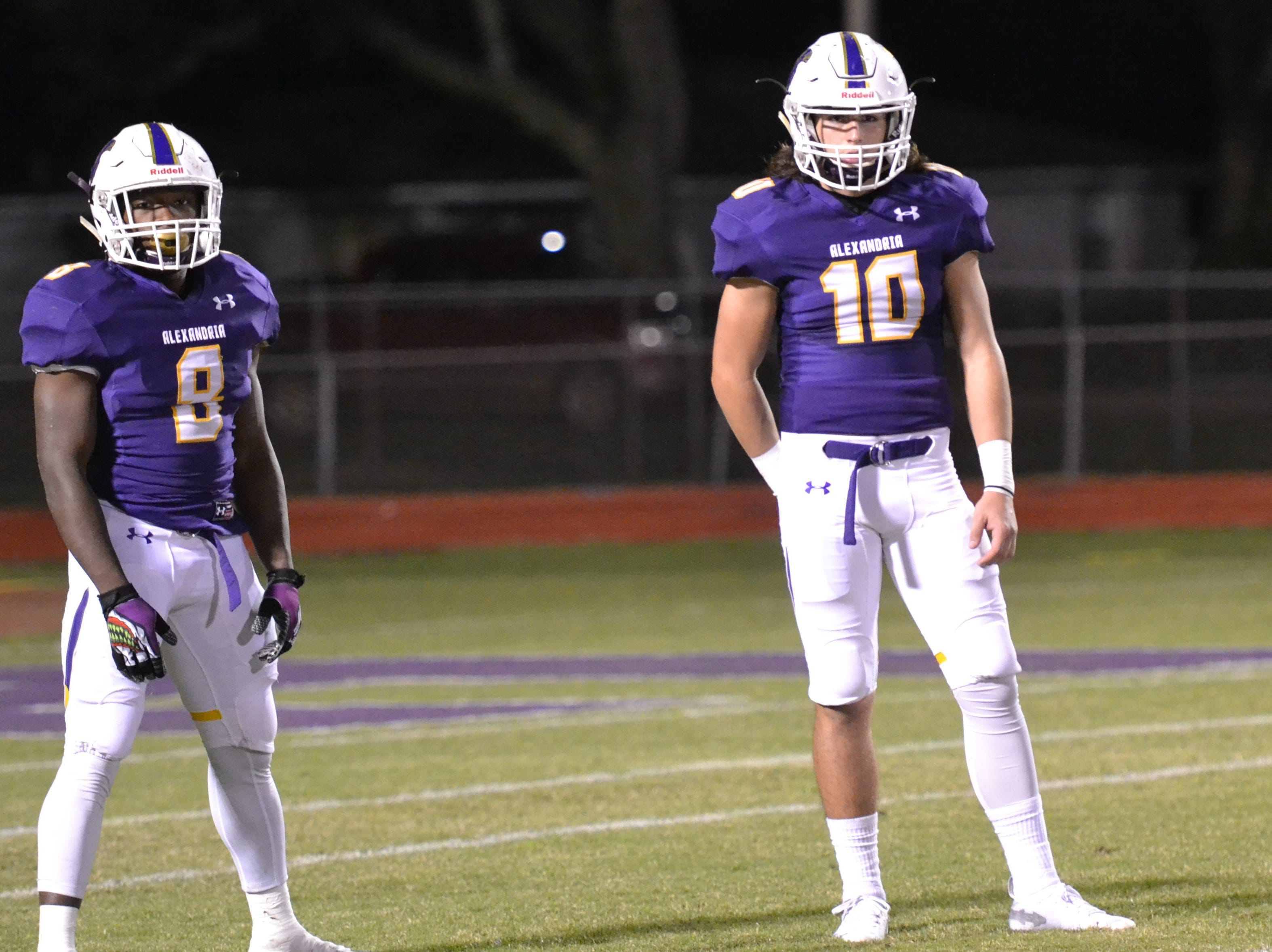 ASH quarterback Ben Hesnis (10) and running back Richard Chark (8) look to the coaches for the play call. The ASH Trojans fell to the Ouachita Parish Lions 42-20 Thursday, Nov. 1, at Alexandria Senior High.