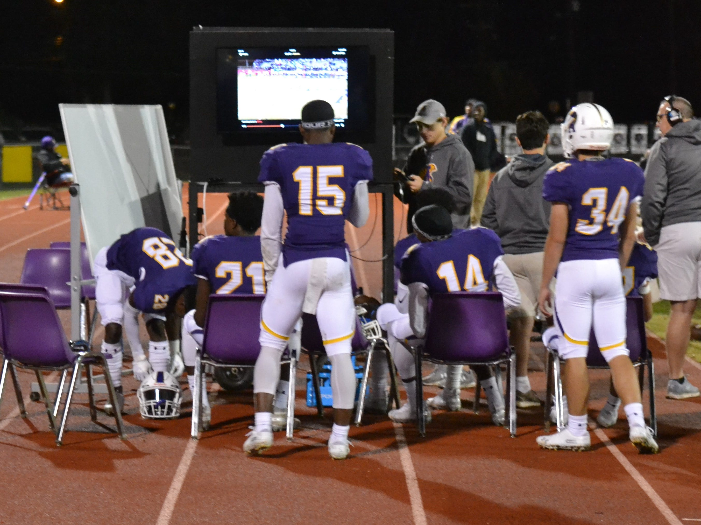 ASH players meet on the sideline to review plays. The ASH Trojans fell to the Ouachita Parish Lions 42-20 Thursday, Nov. 1, at Alexandria Senior High.