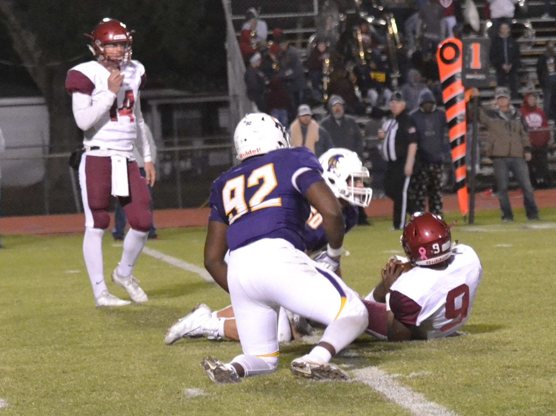 ASH defenders Austin Williams (92) and Dylan Courville (50) team up to take down Ouachita's Dylan Roberts (9) in the backfield for a big loss on a first down play.