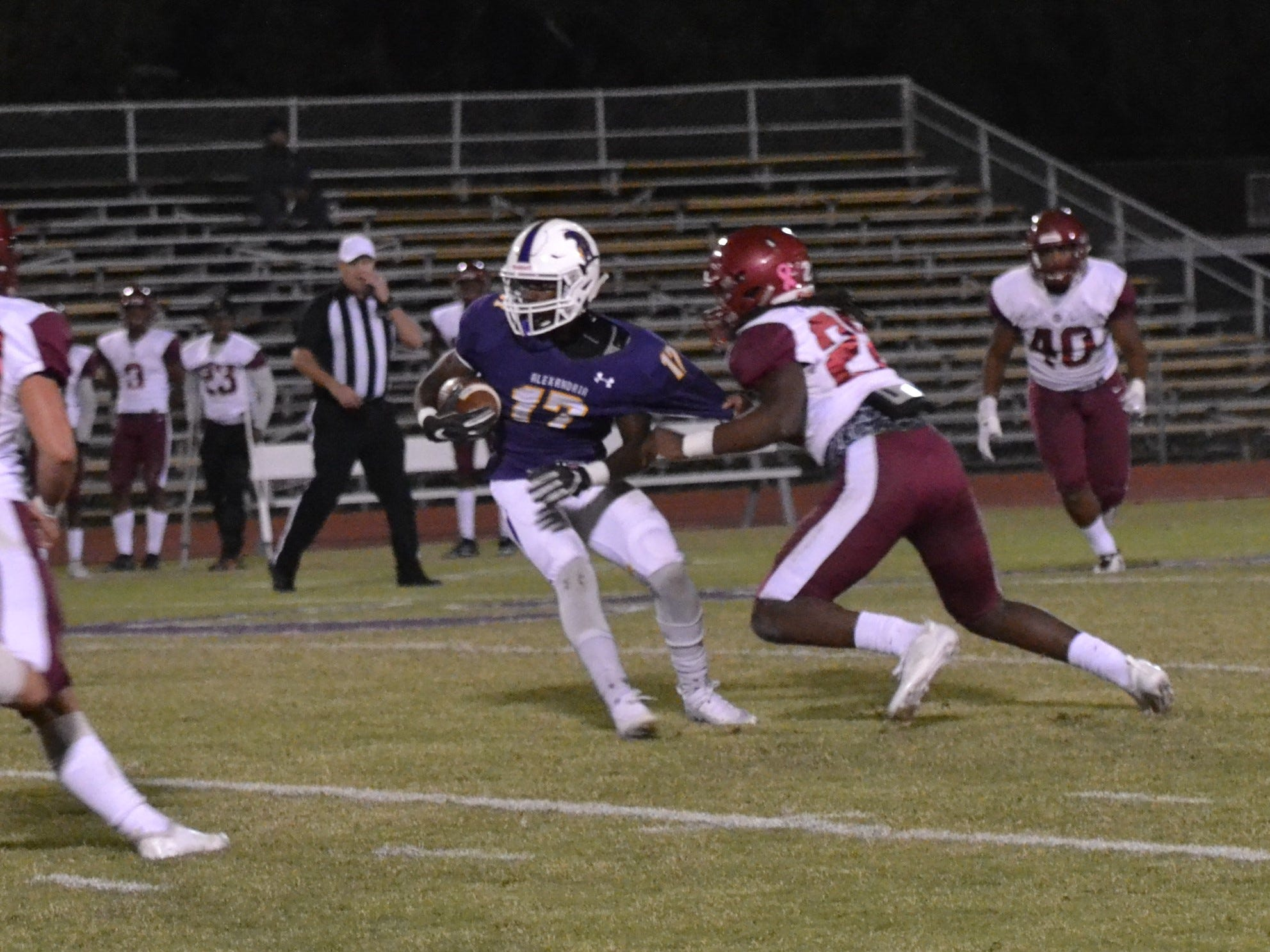 Ouachita defender Elijah Hall (22) tries to make a jersey tackle on ASH wide receiver Darrald More (17). The ASH Trojans fell to the Ouachita Parish Lions 42-20 Thursday, Nov. 1, at Alexandria Senior High.