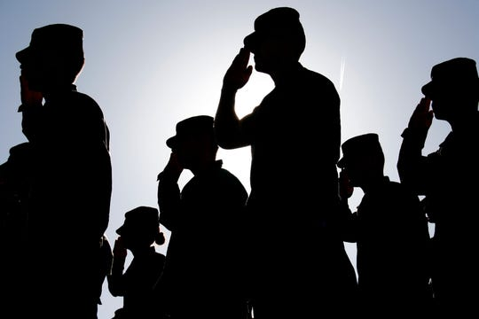 Several soldiers salute the flag at sunset during a military exercise. Army, Marines and Air Force were represented at the ceremony.