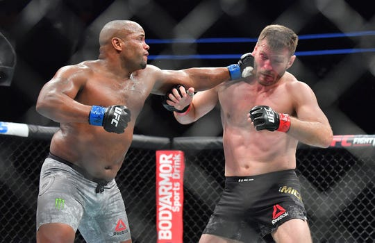 Daniel Cormier (left) lands a punch against Stipe Miocic during their heavyweight championship fight on July 7, 2018 in Las Vegas, Nevada. Cormier won by first-round knockout.