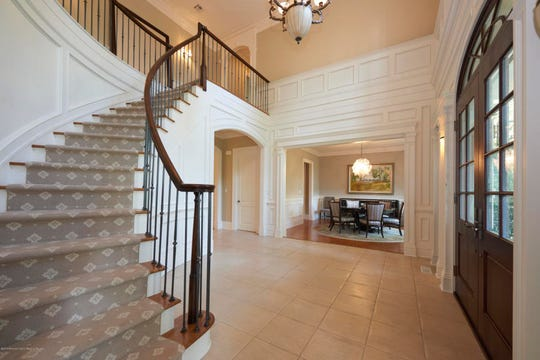 The foyer offers an amazing spiral staircase with amazing decor.