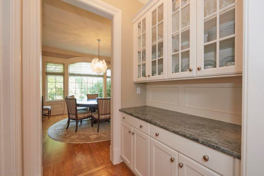 The butler's pantry features granite counter tops and custom cabinets.