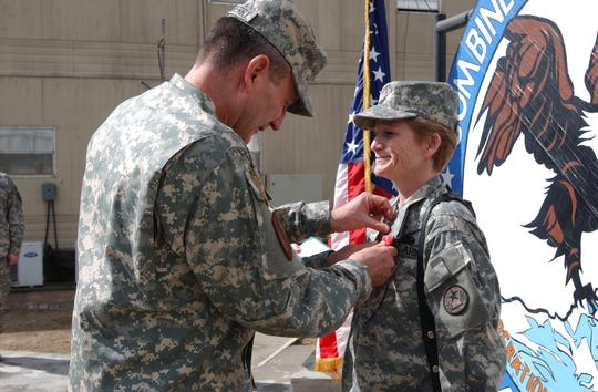 U.S. Army Command Sgt. Maj. Gretchen Evans receives the Bronze Star from Lt. Gen. Karl Eikenberry. Evans served 27 years in the Army before being badly injured in Afghanistan in 2006.