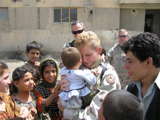 Here pictured at an Afghanistan orphanage, U.S. Army Command Sgt. Maj. Gretchen Evans served 27 years in the U.S. Army. She was badly injured in that country in a 2006 mortar attack.