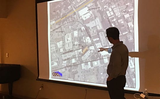 Chris Day, a senior project manager at Civil Design Concepts, shows off plans to renovate Asheville's Flatiron Building on Thursday, Nov. 1 at the Pack Memorial Library in downtown Asheville.